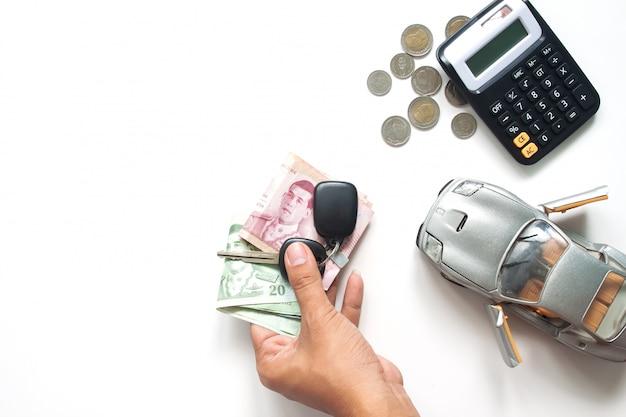 Mensenhand die thaise bankbiljetten en autosleutel, autolening of autofinanciënconcept houden