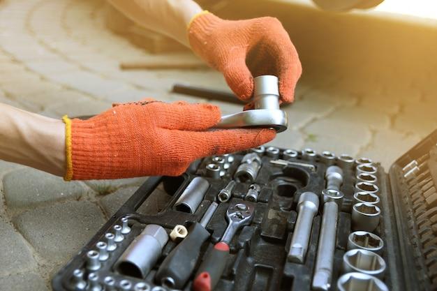 Mensenhand kiest instrument in de autoreparatiedienst van doos.