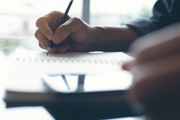 Mensenhand met een potlood dat op blocnote schrijft