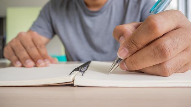 Mensenhand met pen die op notitieboekje schrijven.