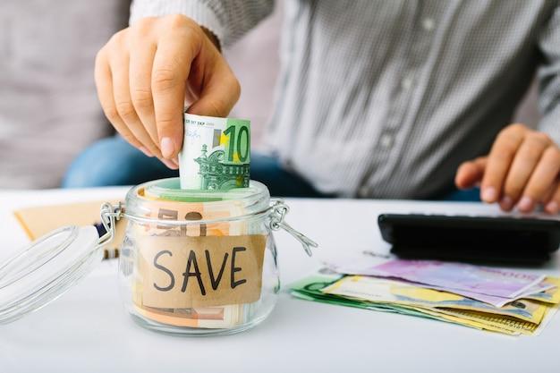 Mensenhand zetten eurobiljetten bankbiljet in een glazen fles om te besparen. man doet zijn boekhouding.