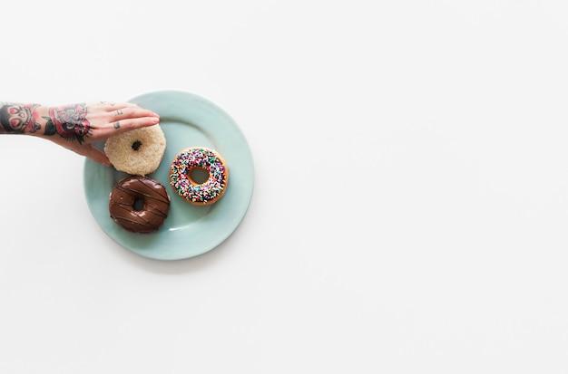 Mensenhanden bereiken donuts op de plaat