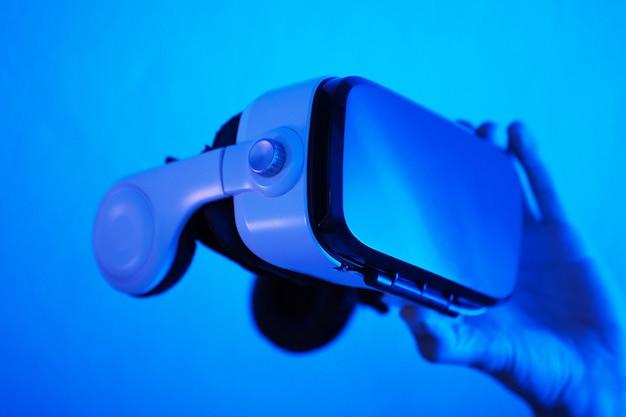 Mensenhanden die 3d 360 vr hoofdtelefoonglazen in futuristisch purper blauw neonlicht houden.