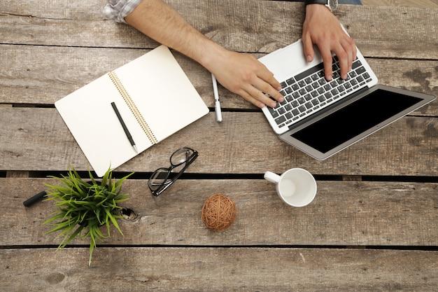 Mensenhanden die aan laptop in zijn bureau hoogste mening werken