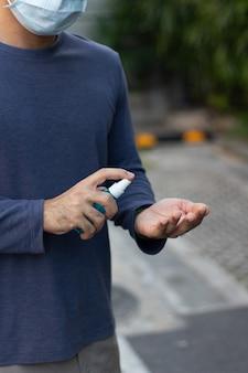 Mensenhanden die alcoholfles spuiten aan handen, covid-19 en coronavirus houden