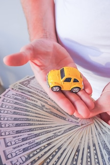 Mensenhanden die dollarrekeningen en gele auto houden