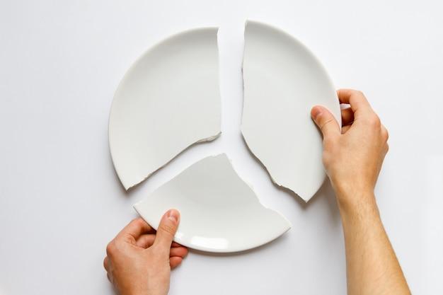 Mensenhanden die een gebroken witte plaat houden. metafoor voor echtscheiding, relaties, vriendschappen, kraken in het huwelijk. liefde is weg