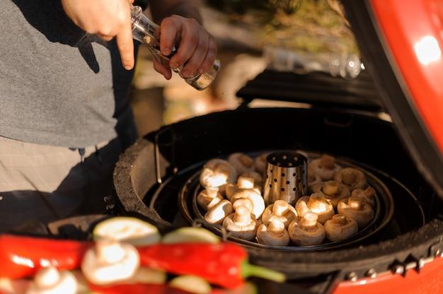 Mensenhanden die kruiden toevoegen die verse champignonspaddestoel bij de grill koken