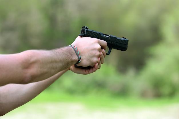 Mensenhanden die met zwart pistool schieten