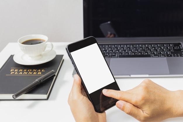 Mensenhanden die mobiele telefoon met laptop computer op lijst met behulp van.