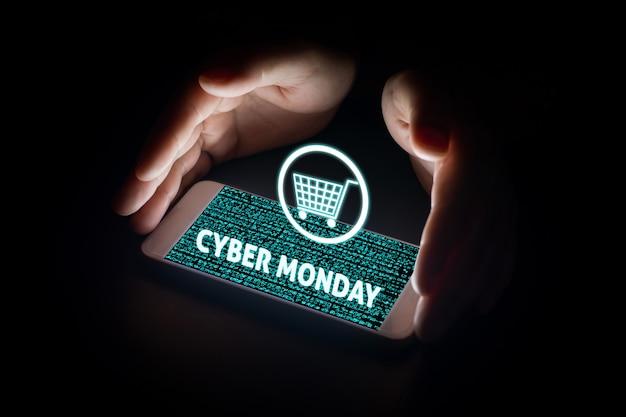 Mensenhanden die slimme telefoon met de tekst en de kar van de cybermaandag op de virtuele schermen op smartphone houden.