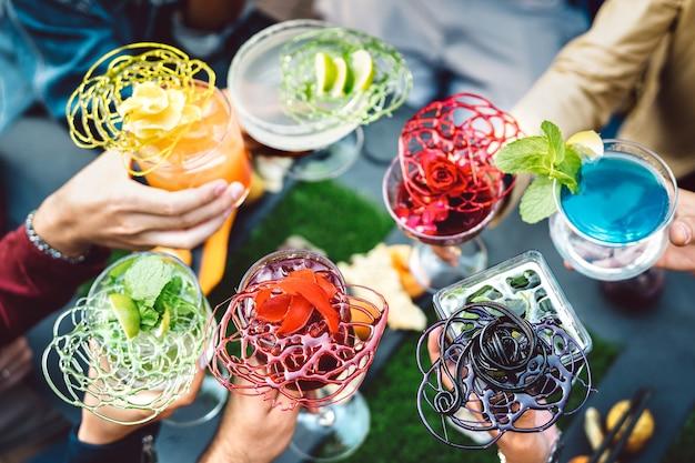 Mensenhanden die veelkleurige chique cocktails roosteren