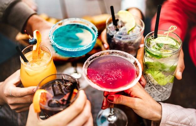 Mensenhanden die veelkleurige luxe drankjes roosteren
