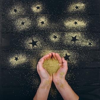 Mensenhanden houden een glanzende gouden glitter in hun handpalmen en gieten deze vormende sterren op een donkere houten tafel.