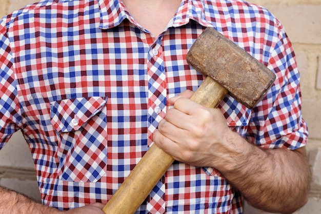 Mensenhanden met een hamer, op de bakstenen muur. werken