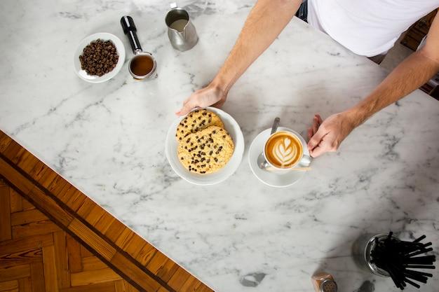 Mensenhanden met koekjes en een cappuccino op de teller