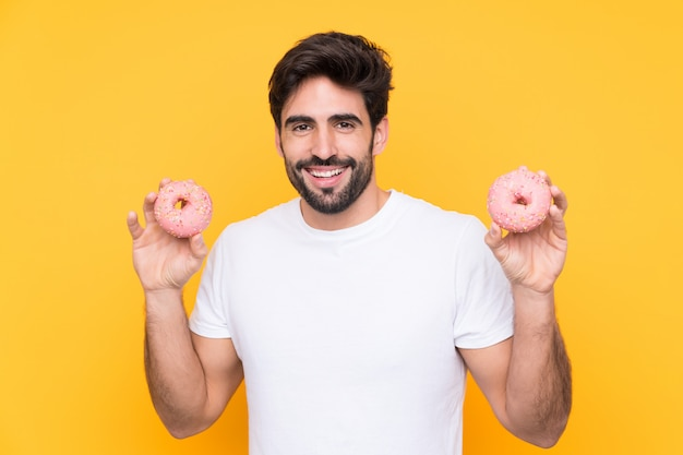 Mensenholding donuts over gele muur