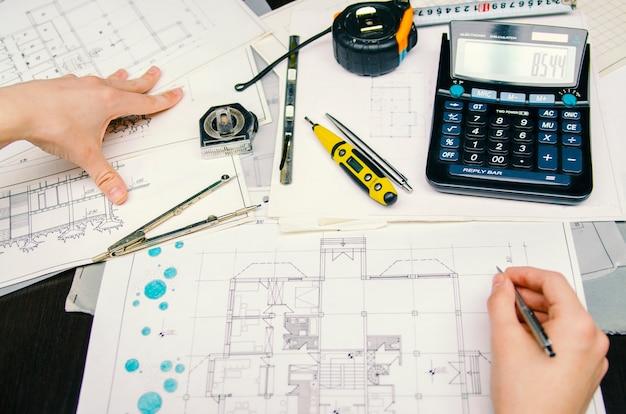 Menseningenieur die aan zijn de bouwplannen werken, die potlood en calculator gebruiken