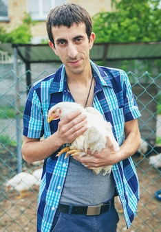 Mensenlandbouwer die een kip in zijn handen houden.