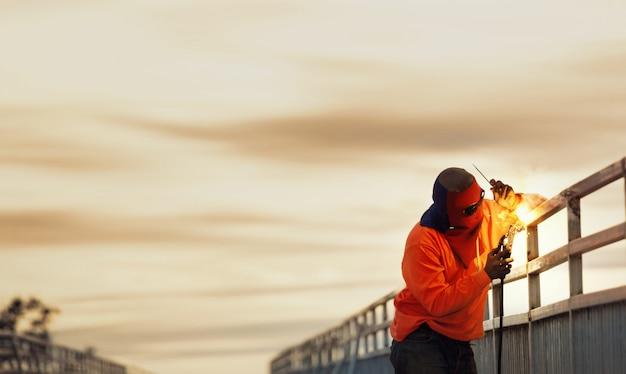 Mensenlasser die bij de brugbouw werken.
