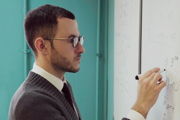 Mensenleraar die met glazen op een whiteboard schrijven