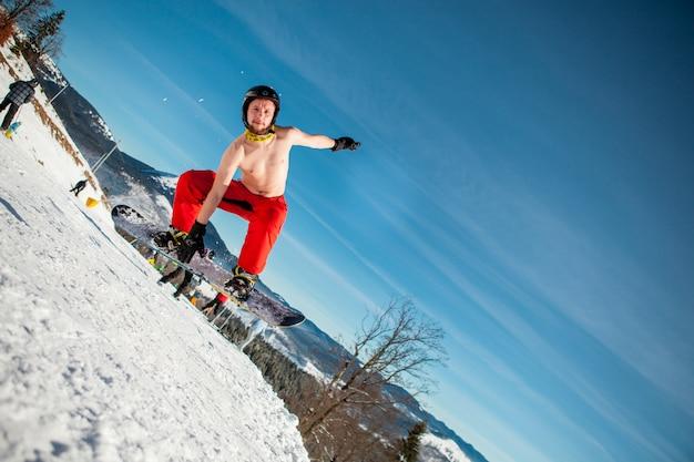 Mensenpensionair die op zijn snowboard tegen de achtergrond van bergen springen