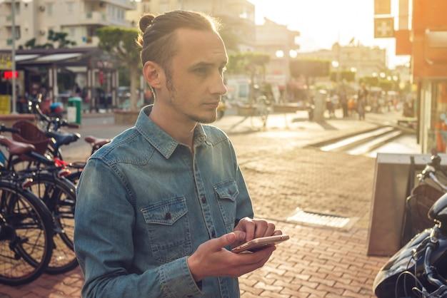 Mensenreiziger die zijn smartphone in de straten van de stad bekijken