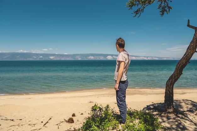 Mensenreiziger het ontspannen op het strand van olkhon-eiland die het water van het meer en de bergen en de blauwe hemel overzien