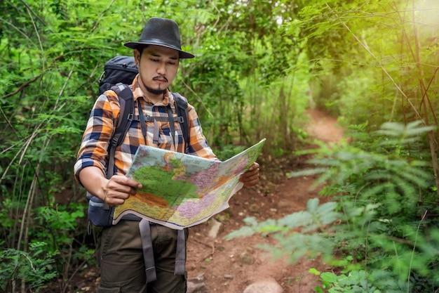 Mensenreiziger met rugzak en kaart die richtingen zoeken in het bos