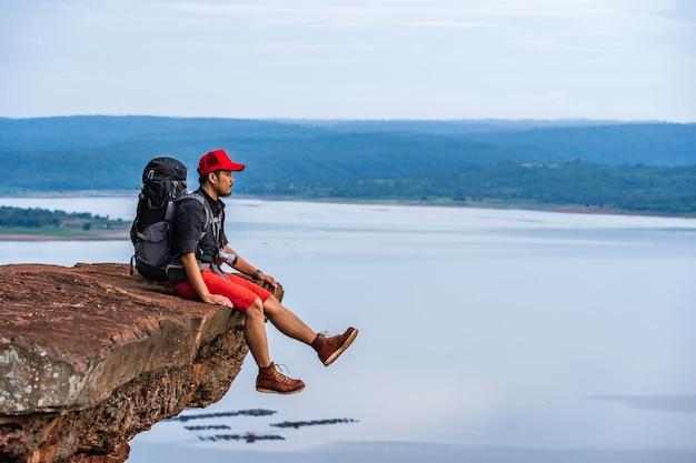 Mensenreiziger met rugzakzitting op rand van klip, op een bovenkant van de rotsberg