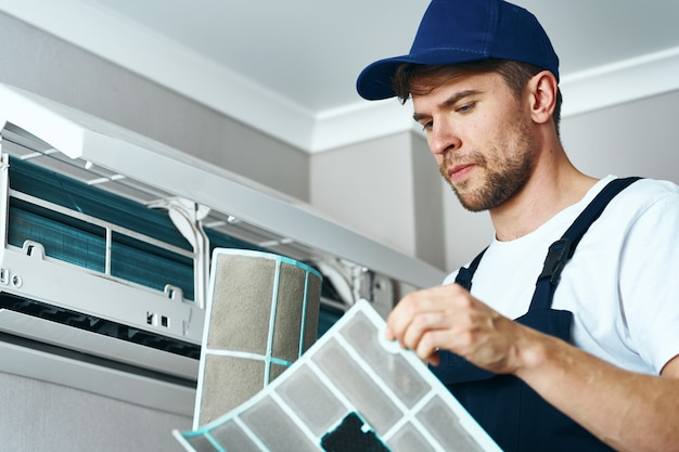 Mensenreparatie en schoonmakende airconditioner, arbeider thuis