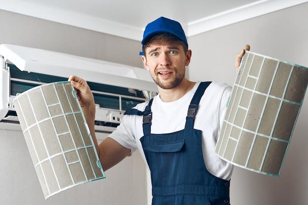 Mensenreparatie en schoonmakende airconditioning, arbeider thuis