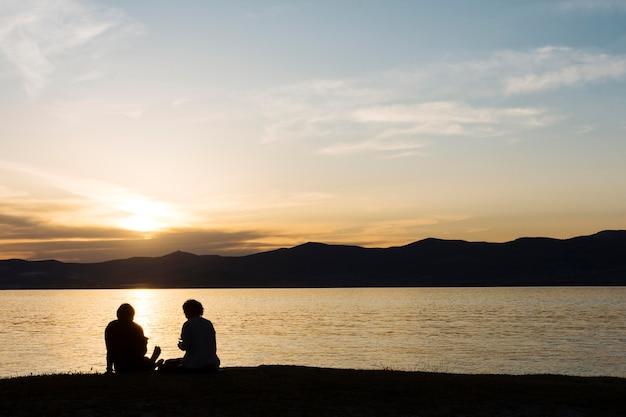 Mensensilhouetten en het strand tijdens zonsondergang