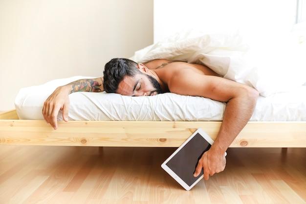 Mensenslaap die op bed digitale tablet houden