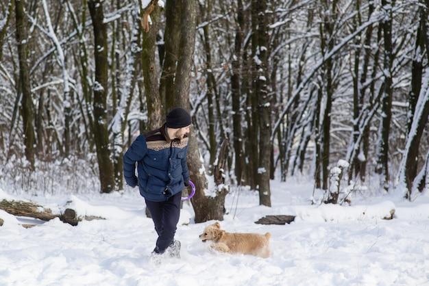 Mensenspel met hond in sneeuwbos