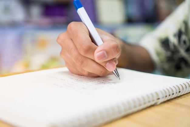 Mensenstudent die en nota's over notitieboekje met pen in bibliotheek nemen schrijven