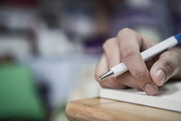 Mensenstudent die en nota's over notitieboekje op universiteitsuniversiteit voor thuiswerk nemen schrijven