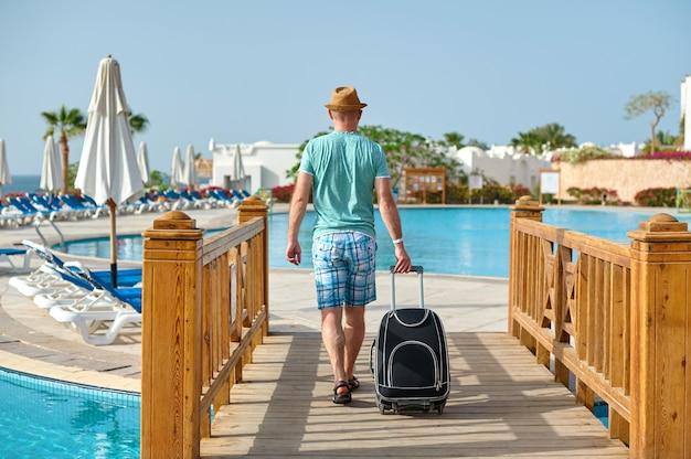 Mensentoerist in de zomerkleren met een koffer in zijn hand, die het overzees op het strand bekijkt