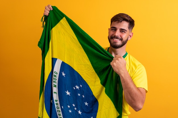 Mensenventilator die een braziliaanse vlag gele achtergrond houdt. brazilië kleuren op de achtergrond, groen, blauw en geel. verkiezingen, voetbal of politiek.