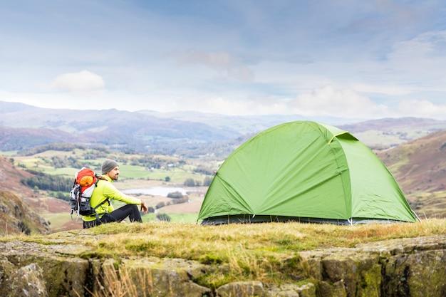 Mensenverkenner met een tent bovenop berg