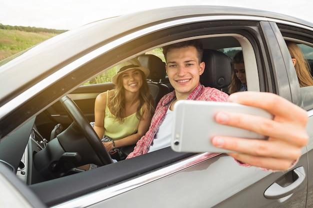 Mensenzitting in de auto met zijn meisje die selfie op smartphone nemen