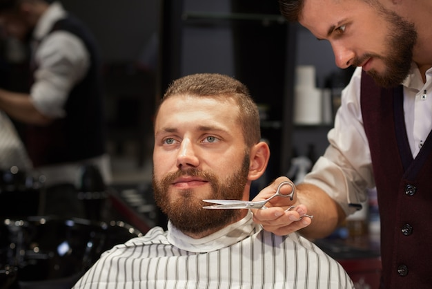 Mensenzitting in kapperswinkel en het krijgen van knipsel van baard