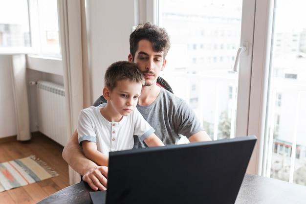 Mensenzitting met zijn zoon die laptop met behulp van