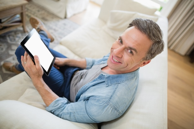 Mensenzitting op bank en het gebruiken van digitale tablet in woonkamer