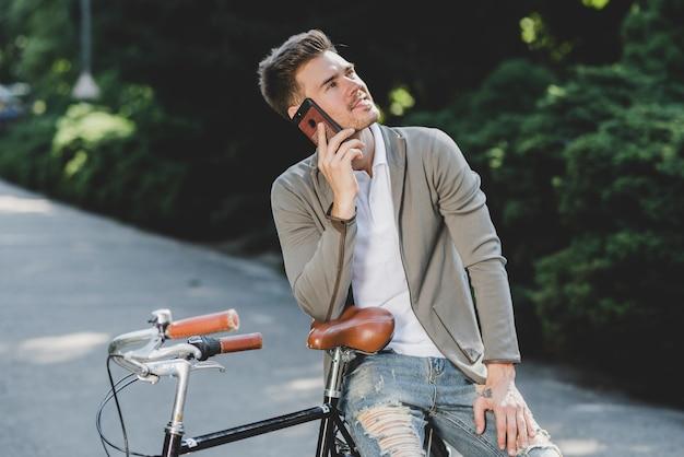 Mensenzitting op fiets die op mobiele telefoon spreken