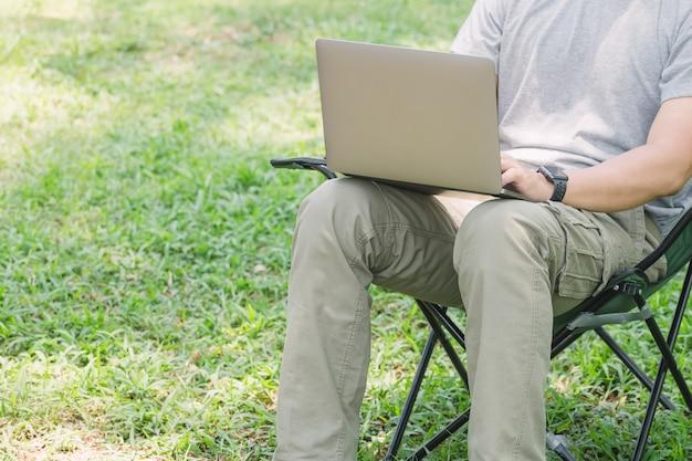 Mensenzitting op het kamperen stoel en het werken met laptop computer in de tuin