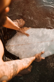 Mensenzitting op witte surfplank in water
