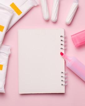 Menstruatie bij vrouwen. een leeg notitieboekje naast een stift, maandverband en tampons.