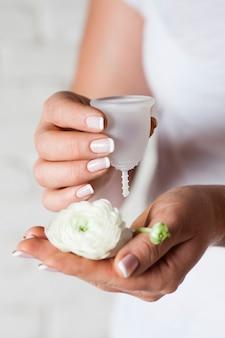Menstruatiecup in vrouwelijke handen. vrouw houdt bloem en siliconen hygiënebeker vast, nieuw apparaat om afval te minimaliseren en het milieu te beschermen