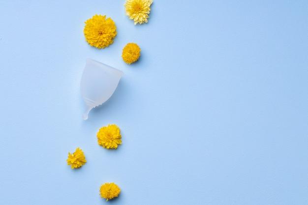 Menstruatiecup met bloemen op blauwe achtergrond